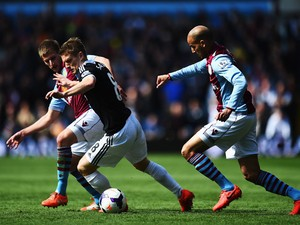 Steven Davis of Southampton holds off Marc Albrighton and Karim El Ahmadi of Aston Villa during the Barclays Premier League match between Aston Villa and Southampton at Villa Park on April 19, 2014