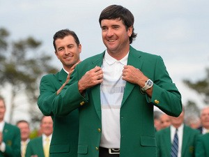 2014 Masters champion Bubba Watson receives his green jacket from last year's winner Adam Scott at Augusta National Golf Club, Georgia on April 13, 2014