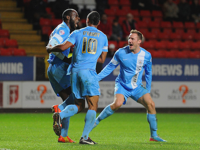 Jean-Yves Mvoto of Barnsley celebrates scoring the opening goal with Chris O'Grady and Liam Lawrence of Barnsley during the Sky Bet Championship match against Charlton on April 15, 2014