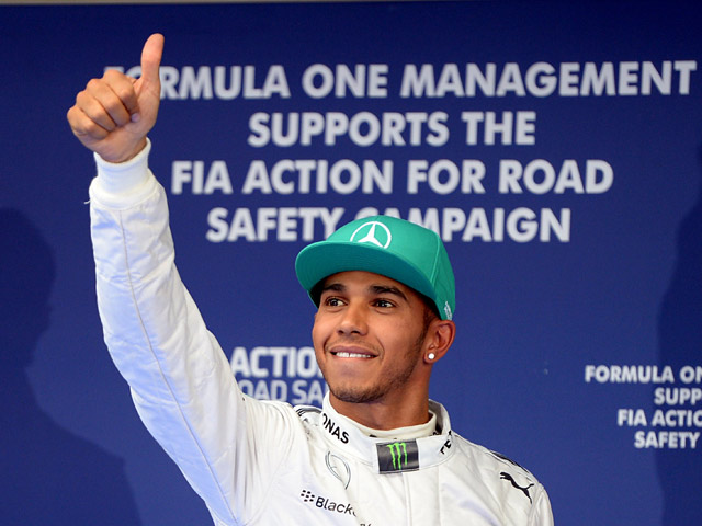 Lewis Hamilton of Mercedes celebrates after qualifying in pole position for the F1 Chinese Grand Prix on April 19, 2014