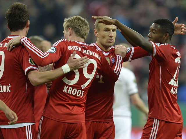 Bayern's Toni Kroos celebrates with team mates after scoring his team's second goal against Kaiserslautern during the DFB-Pokal semi-final match on April 16, 2014