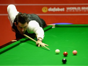 Ronnie O'Sullivan plays a shot against Joe Perry during their second round match in The Dafabet World Snooker Championship at Crucible Theatre on April 26, 2014