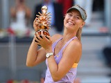 Maria Sharapova celebrates with the trophy after beating Simona Halep in the Madrid Masters final on May 11, 2014