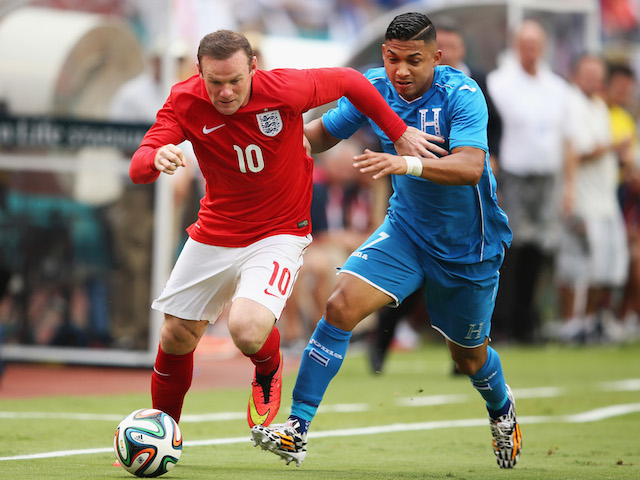 Wayne Rooney of England holds off Emilio Izaguirre of Honduras in the first half during the International Friendly match on June 7, 2014