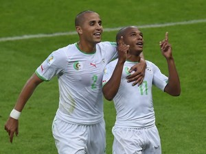 Algeria's midfielder Yacine Brahimi (R) celebrates with defender Madjid Bougherra after scoring his team's fourth goal during the Group H football match against South Korea on June 22, 2014