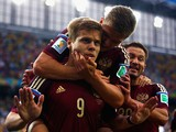 Alexander Kokorin of Russia celebrates scoring his team's first goal with teammate Oleg Shatov on his back during the 2014 FIFA World Cup Brazil Group H match between Algeria and Russia at Arena da Baixada on June 26, 2014