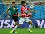 Croatia's defender Vedran Corluka (R) and Mexico's forward Oribe Peralta vie for the ball during a Group A football match on June 23, 2014