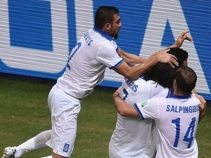 Greece's players celebrate after scoring a goal during the Group C football match between Greece and Ivory Coast at the Castelao Stadium in Fortaleza during the 2014 FIFA World Cup on June 24, 2014