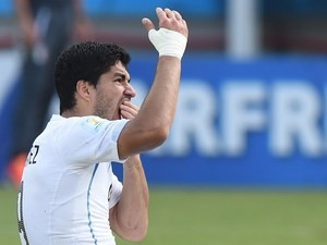 Uruguay forward Luis Suarez puts his hand to his mouth after clashing with Italy's defender Giorgio Chiellini during a Group D football match on June 24, 2014