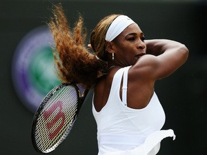 Serena Williams of the United States hits a forehand return during her Ladies' Singles third round match against Alize Cornet on June 28, 2014