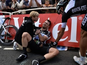 Britain's Mark Cavendish injured receives medical assistance after a fall near the finish line at the end of the 190.5 km first stage of the 101st edition of the Tour de France on July 5, 2014