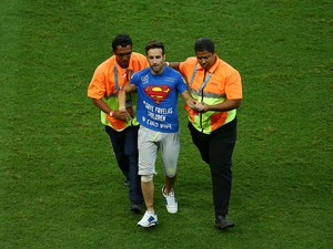 A pitch invader is taken off the field by security during the 2014 FIFA World Cup Brazil Round of 16 match between Belgium and the United States at Arena Fonte Nova on July 1, 2014
