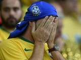 Brazilian fan react during the semi-final football match between Brazil and Germany at The Mineirao Stadium in Belo Horizonte during the 2014 FIFA World Cup on July 8, 2014