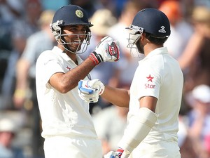 India's Mohammed Shami and India's Bhuvneshwar Kumar celebrate after scoring a half century during the second days play in the first cricket Test match between England and India at Trent Bridge in Nottingham, central England on July 10, 2014