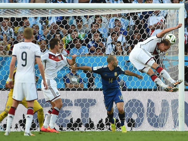 Germany's defender Benedikt Hoewedes (R) heads the ball towards the goal as Argentina's midfielder Javier Mascherano (C) and Germany's forward Miroslav Klose watch on during the World Cup final on July 13, 2014