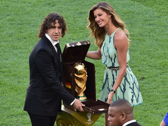 Spanish defender Carles Puyol (L) poses with the World Cup (C) and Brazilian model Gisele Bundchen (R) during a closing ceremony ahead of the final football match on July 13, 2014