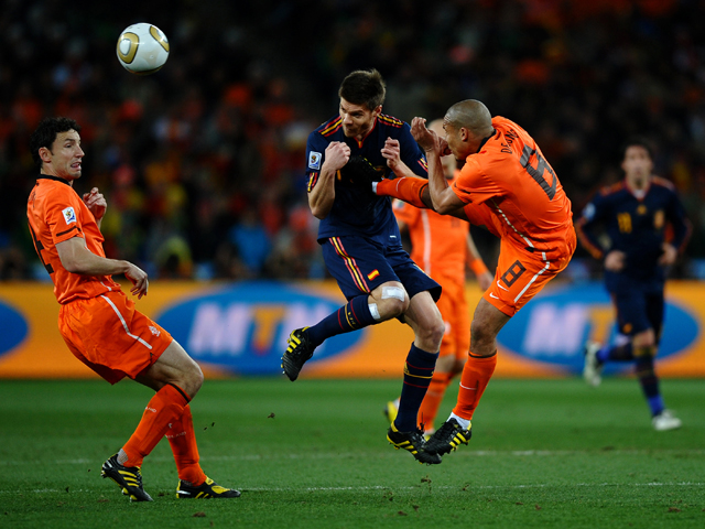 Nigel De Jong of the Netherlands tackles Xabi Alonso of Spain during the 2010 FIFA World Cup South Africa Final match between Netherlands and Spain at Soccer City Stadium on July 11, 2010