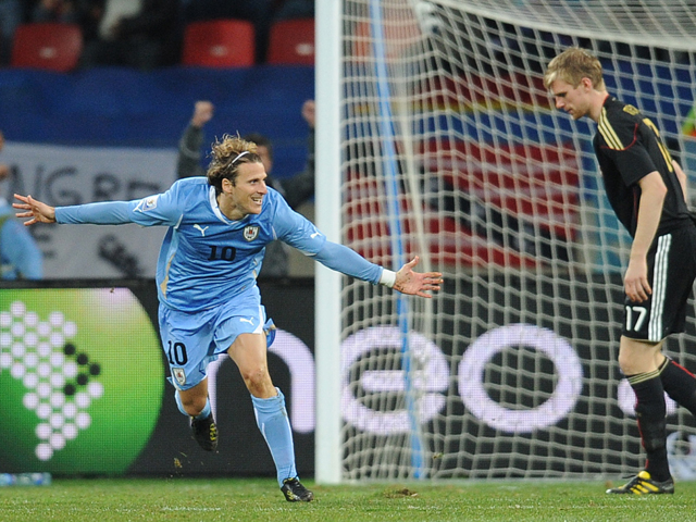 Uruguay's striker Diego Forlan celebrates after scoring as Germany's defender Per Mertesacker dejects during the 2010 World Cup third place match Uruguay vs Germany on July 10, 2010