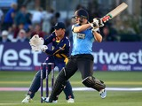 Luke Wright of Sussex hits out while Mark Wallace of Glamorgan looks on during the Natwest T20 Blast match between Sussex Sharks and Glamorgan at The BrightonAndHoveJobs.com County Ground on July 15, 2014
