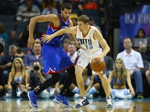 Michael Carter-Williams #1 of the Philadelphia 76ers tries to steal the ball from Luke Ridnour #13 of the Charlotte Bobcats during their game at Time Warner Cable Arena on April 12, 2014