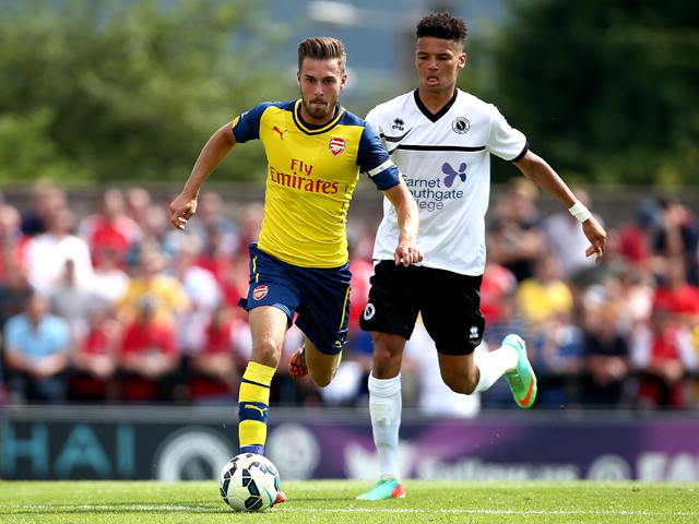 Aaron Ramsey of Arsenal tackles with Lee Angol of Boreham Wood during the pre season friendly match between Borehamwood and Arsenal at Meadow Park on July 19, 2014