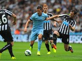 Newcastle player Mike Williamson challenges Stevan Jovetic during the Barclays Premier League match between Newcastle United and Manchester City at St James' Park on August 17, 2014