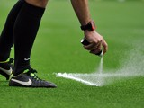 Referee Mike Dean uses vanishing spray to mark the pitch for a free kick during the English Premier League football match between Manchester United and Swansea City at Old Trafford in Manchester, north west England on August 16, 2014