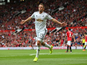 Gylfi Sigurdsson of Swansea City celebrates scoring his team's second goal during the Barclays Premier League match between Manchester United and Swansea City at Old Trafford on August 16, 2014