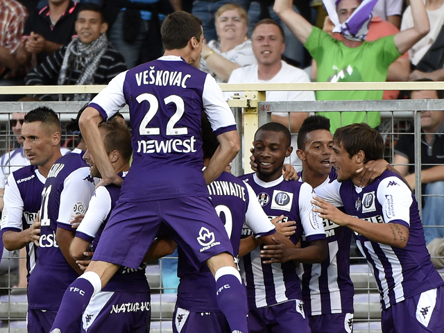 Toulouse's French-Ivorian defender Jean Akpa-Akpro celebrates with teammates after scoring a goal during the French L1 football match between Toulouse (TFC) and Lyon (OL) on August 16, 2014