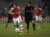 Besiktas's Ismail Koybasi fights for the ball with Arsenal's Jack Wilshere during their UEFA Champions League play-off first leg football match at the Ataturk Olympic Stadium in Istanbul, on August 19, 2014