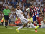 Real Madrid's defender Daniel Carvajal vies with Atletico Madrid's Croatian forward Mario Mandzukic during the Spanish Supercup first-leg football match Real Madrid CF vs Club Atletico de Madrid at the Santiago Bernabeu stadium in Madrid on August 19, 201
