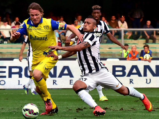 Juventus' Chilean midfielder Arturo Vidal vies with Chievo Verona's French defender Nicolas Frey during the Serie A football match Chievo Verona vs Juventus at the Bentegodi Stadium in Verona on August 30, 2014