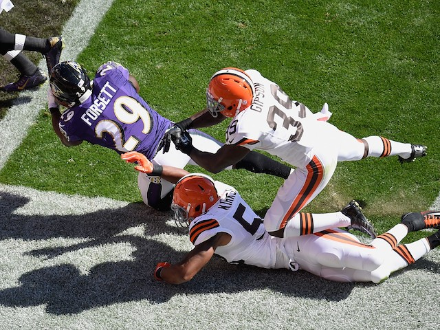 Justin Forsett #29 of the Baltimore Ravens gets dragged down by Tashaun Gipson #39 and Christian Kirksey #58 of the Cleveland Browns on September 21, 2014