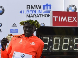 Kenya's Dennis Kimetto poses with his gold medal next to a display showing the time in which he won the 41th edition of the Berlin Marathon in Berlin on September 28, 2014
