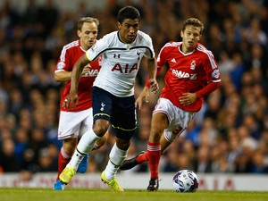 Paulinho of Tottenham Hotspur moves away from Jorge Grant of Nottingham Forest during the Capital One Cup third round match between Tottenham Hotspur and Nottingham Forest at White Hart Lane on September 24, 2014