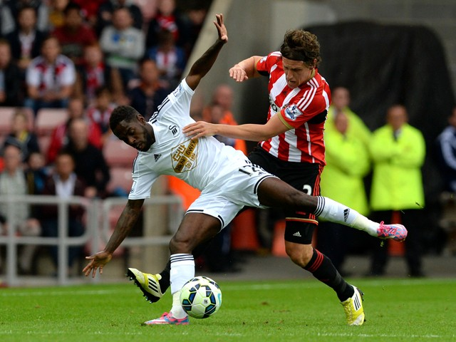 Nathan Dyer of Swansea City is tackled by Billy Jones of Sunderland during the Barclays Premier League match between Sunderland and Swansea City at Stadium of Light on September 27, 2014
