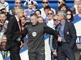 Chelsea's Portuguese manager Jose Mourinho (R) and Arsenal's French manager Arsene Wenger (L) are kept apart by the fourth offici