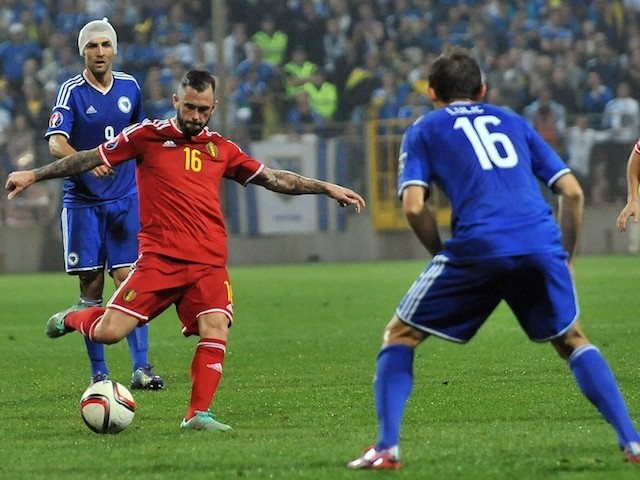 Belgium's Steven Defour (C) strikes the ball, flanked by Bosnia and Herzegovina's Vedad Ibisevic (L) and Senad Lulic (R) during the Euro 2016 qualifying match on October 13, 2014