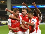 Arsenal's Polish-born German striker Lukas Podolski celebrates with teammates after scoring during a UEFA Champions League