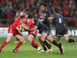 Ian Keatley of Munster is tackled by Brad Barritt during the European Rugby Champions Cup match between Munster and Saracens at Thomond Park on October 24, 2014