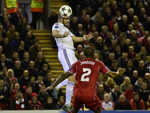 Real Madrid's French forward Karim Benzema rises above Liverpool's English defender Glen Johnson to score Real Madrid's second goal during the UEFA Champions League, group B, football match between Liverpool and Real Madrid at Anfield in Liverpool, northw