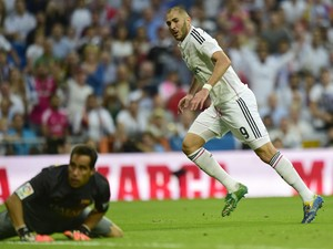 Real Madrid's French forward Karim Benzema looks to Barcelona's goalkeeper Claudio Bravo after scoring during the Spanish league football match Real Madrid CF vs FC Barcelona at the Santiago Bernabeu stadium in Madrid on October 25, 2014