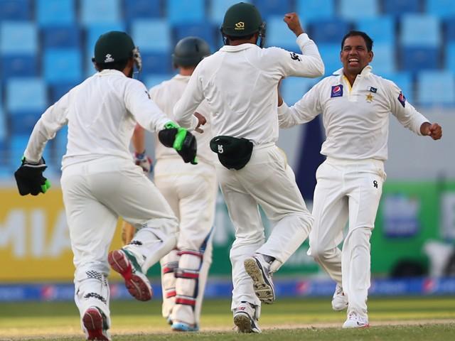 Pakistani bowler Zulfiqar Babar celebrates the dismissal of Australian batsman David Warner during the fourth day of the first test cricket match between Pakistan and Australia at Dubai International Stadium in Dubai on October 25, 2014
