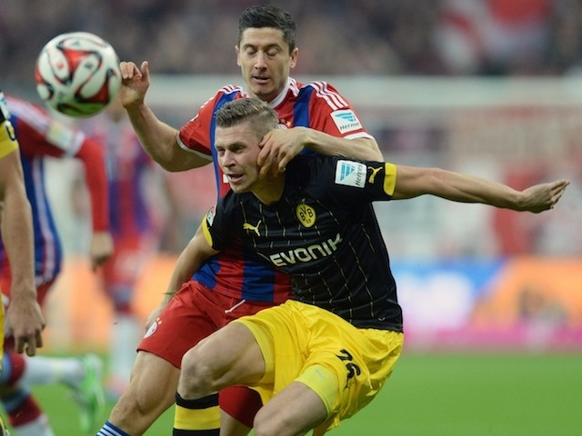 Bayern Munich's Polish striker Robert Lewandowski and Dortmund's Polish defender Lukasz Piszczek (front) vie for the ball during the German first division Bundesliga football match on November 1, 2014