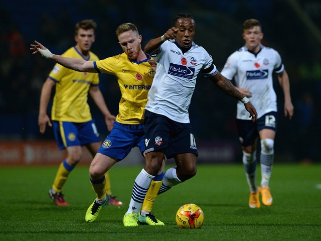 Neil Danns of Bolton Wanderers is tackled by Adam Forshaw of Wigan Athletic during the Sky Bet Championship match between Bolton Wanderers and Wigan Athletic at Macron Stadium on November 7, 2014