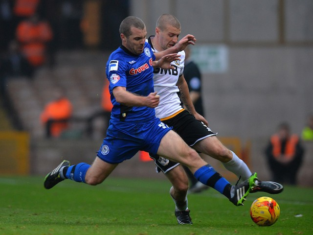 Carl Dickinson of Port Vale is tackled by Stephen Dawson of Rochdale during the Sky Bet League One match between Port Vale and Rochdale at Vale Park on November 15, 2014