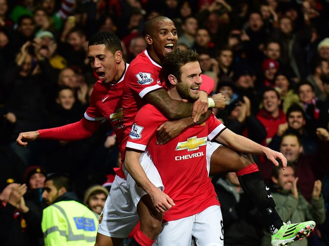 Manchester United's Spanish midfielder Juan Mata is congratulated by Manchester United's English midfielder Ashley Young and Manchester United's English defender Chris Smalling after scoring their second goal during the English Premier League football mat