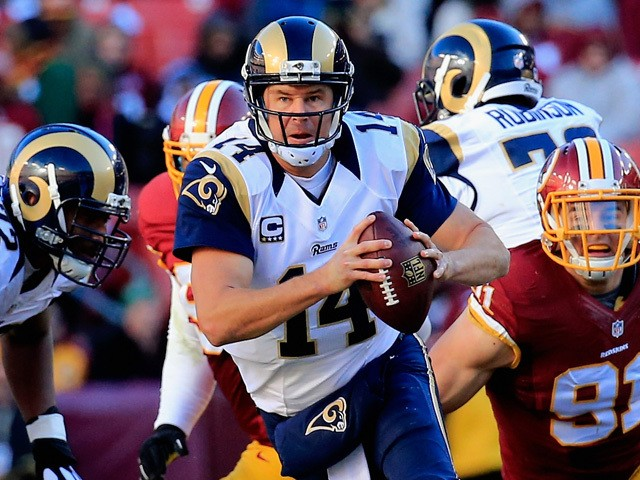 Quarterback Shaun Hill #14 of the St. Louis Rams scrambles to avoid the pressure of outside linebacker Ryan Kerrigan #91 of the Washington Redskins in the second quarter of a game at FedExField on December 7, 2014