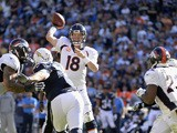 Quarterback Peyton Manning #18 of the Denver Broncos looks to pass agianst the San Diego Chargers defense at Qualcomm Stadium on December 14, 2014