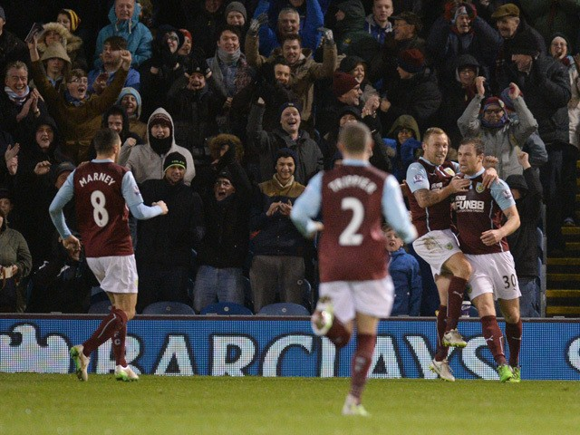 Burnley players celebrate with Burnley's English striker Ashley Barnes after he scores the opening goal of the English Premier League football match between Burnley and Southampton at Turf Moor in Burnley, north west England, on December 13, 2014